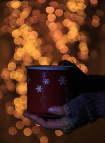 Gloved hands, festive background, hot drink, bokeh, Christmas